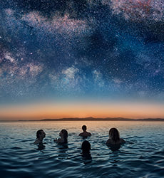 People swimming in sea under a starry sky