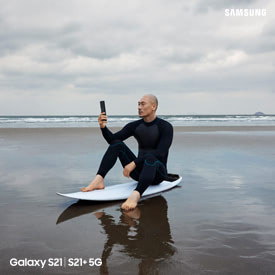 man on surf board on the beach taking a photo